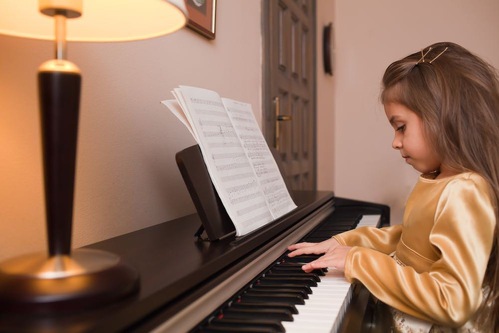 picture of a child playing the piano with score on the music stand