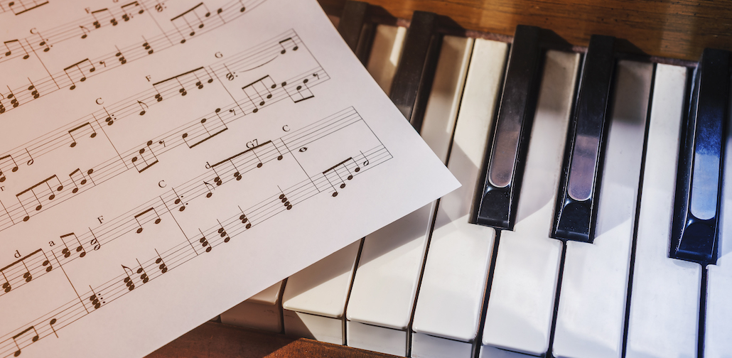 Piano keyboard with sheet music, ready for piano lessons in New York!