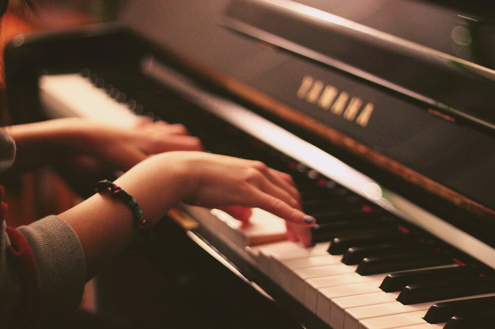 Hands playing a Yamaha piano keyboard