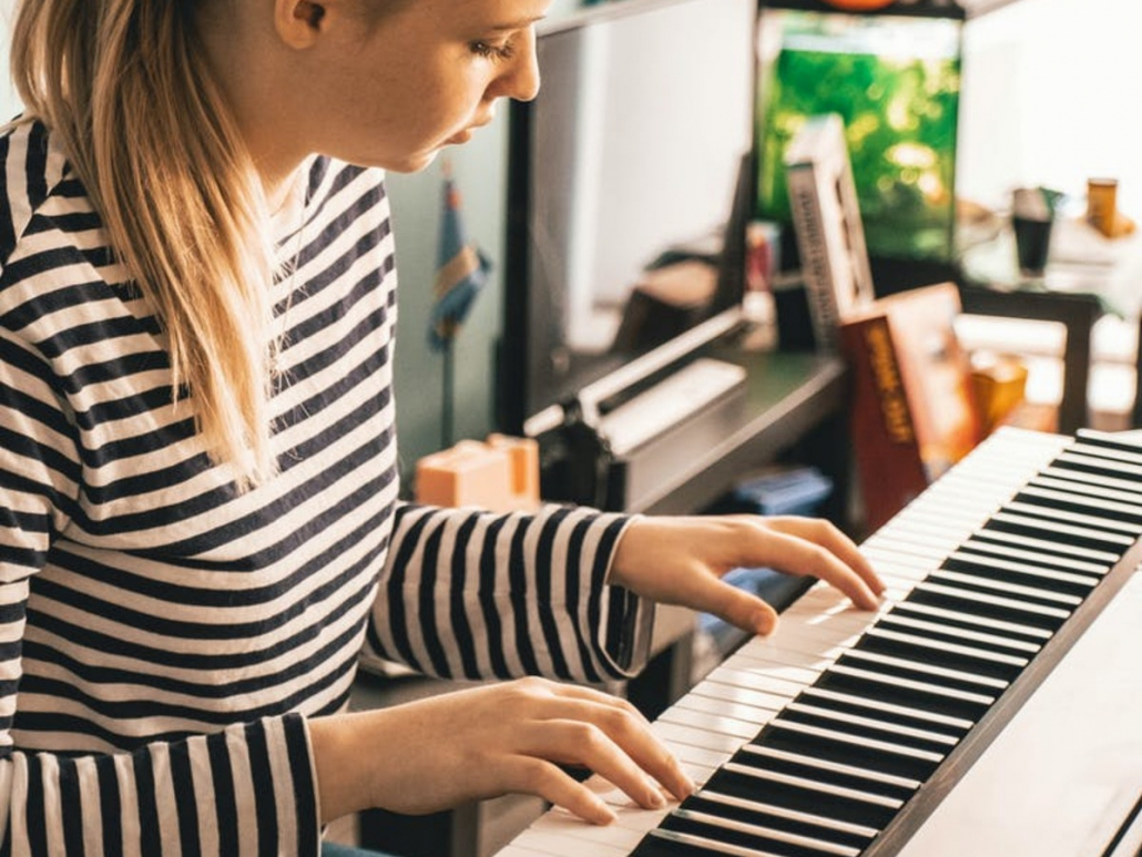 Picture of a woman playing the piano at a piano lesson.