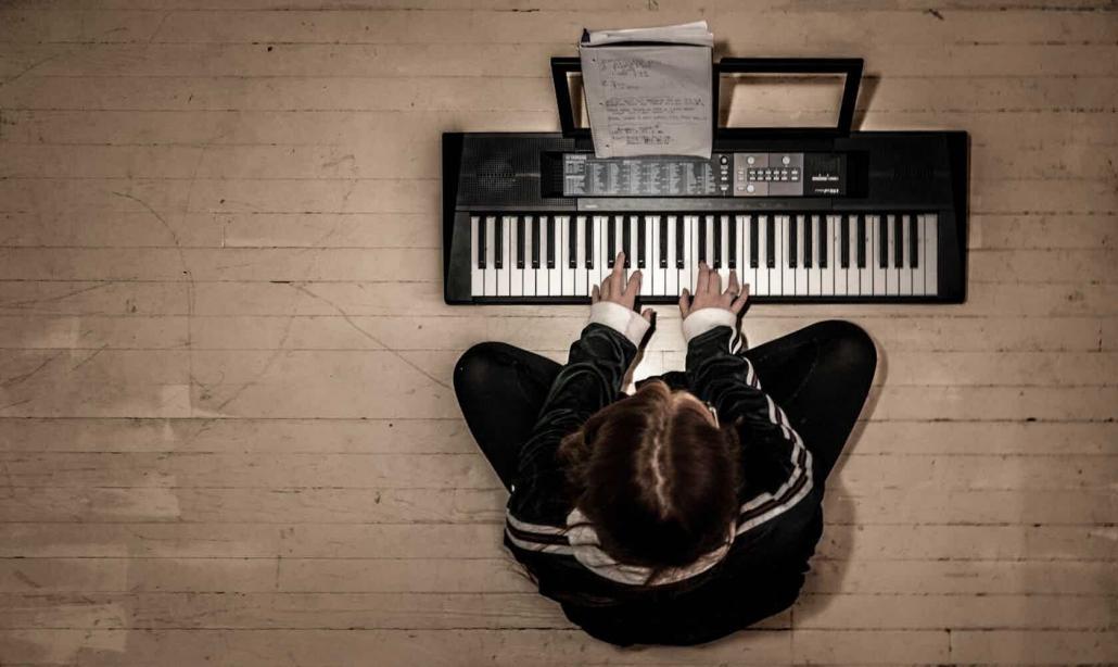 man playing a digital (midi) keyboard on a wood floor