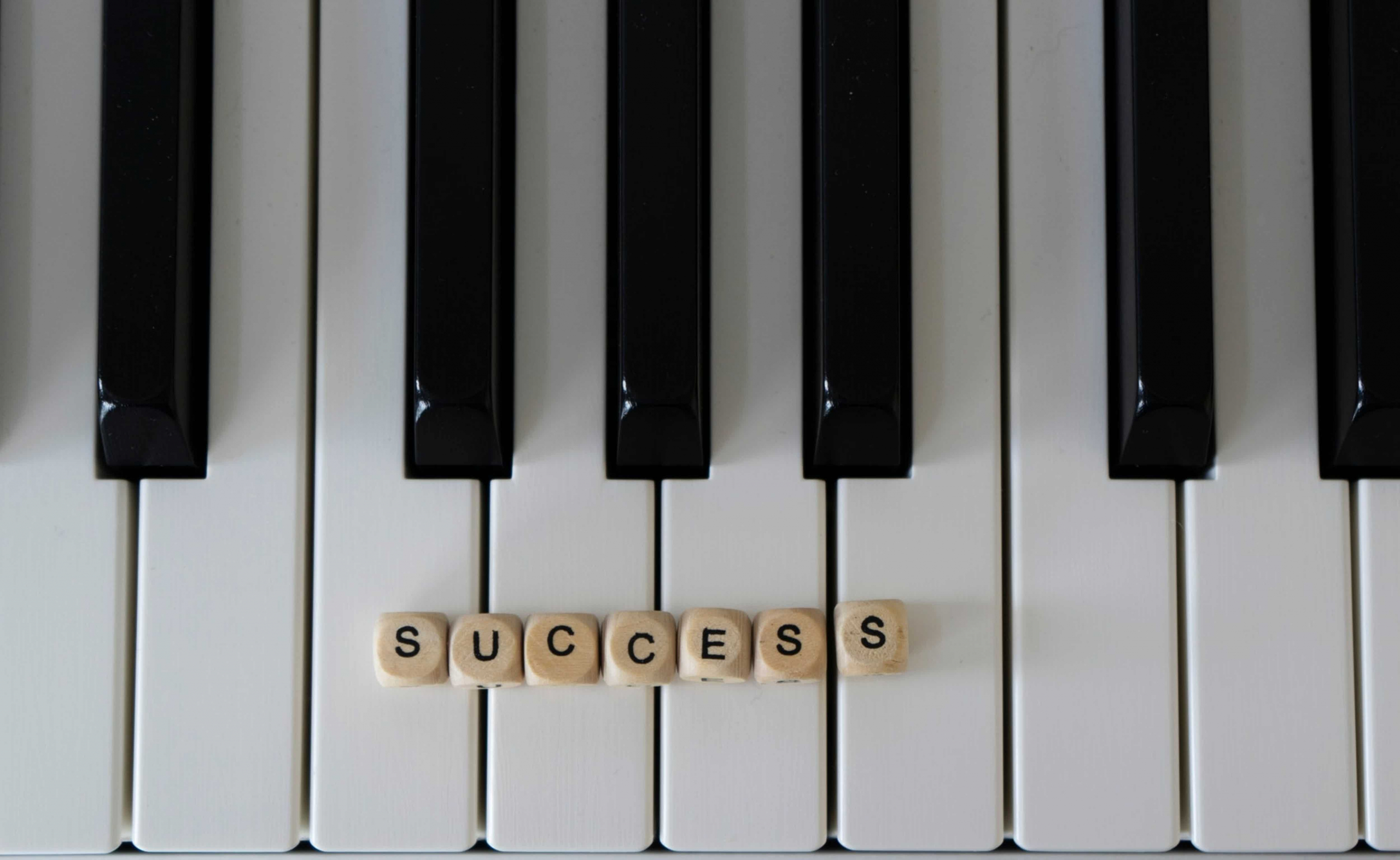 close-up of piano keys with 'success' spelled out in dice
