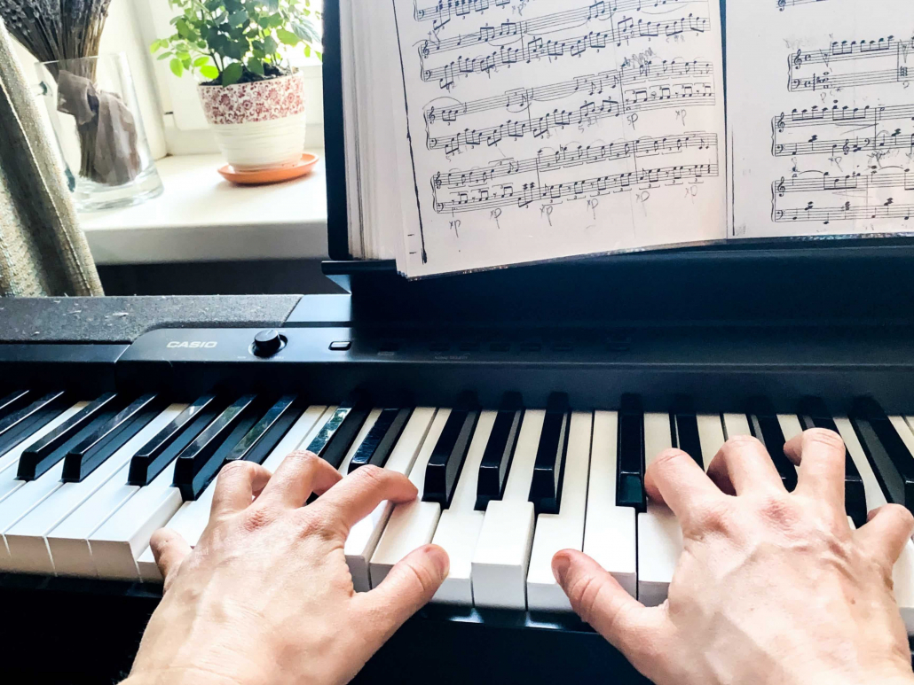 hands playing a digital keyboard with sheet music and a green plant